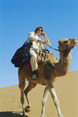 Man with mobile phone riding camel in desert — Stock Photo