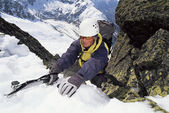 Mountaineer using an ice axe to climb a steep slope — Stock Photo