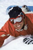 Young snowboarder lying in the snow — Stok fotoğraf