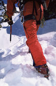 Close-up of young man mountain climbing on snowy peak — Stock Photo