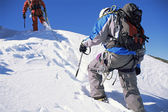 Young men mountain climbing on snowy peak — Stock Photo