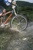 Mountain biker crossing stream — Stock Photo