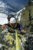 Mountaineer scaling snowy rock face — Stock Photo