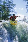Młody człowiek, spływy kajakowe na wodospad — Zdjęcie stockowe
