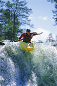 Young man kayaking on waterfall — ストック写真