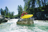 Kayaker perched on boulder in river — Stock Photo