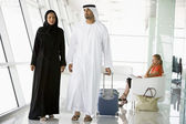 Couple walking through airport departure lounge — Stock Photo