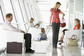 Passengers waiting in airport departure lounge — Stockfoto