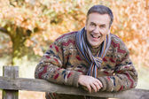 Senior man resting on fence — Stock Photo