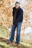 Young man clearing autumn leaves — Stockfoto
