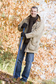 Man tidying autumn leaves — Stockfoto