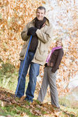 Couple clearing autumn leaves — Stockfoto