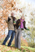 Young couple having fun with autumn leaves — Stok fotoğraf