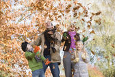 Family throwing leaves in the air — Stock fotografie