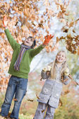 Two children throwing leaves in the air — Stock Photo