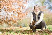 Mulher sênior recolha das folhas na caminhada — Foto Stock