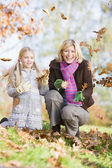 Mother and daughter throwing leaves in the air — Stock Photo