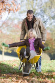 Man pushing wife in wheelbarrow — Stock Photo