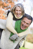 Senior man giving woman piggyback ride — Stock Photo