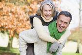 Senior mannen ger kvinnan piggyback ride — Stockfoto