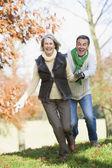 Senior man chasing woman through countryside — Stock Photo