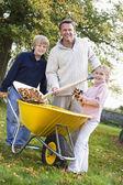 儿童帮助父亲收集秋天的树叶 — 图库照片