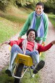 Son pushing mother in wheelbarrow — Stock Photo