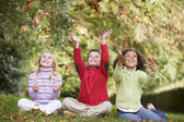 Group of children playing in autumn leaves — Stock Photo