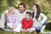Family relaxing in autumn woodlands — Stock Photo