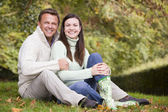 Couple sitting in autumn woods — Stock Photo