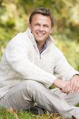 Muž sedí venku v podzimní krajině — Stock fotografie