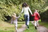 Mother and children running along woodland path — Stock Photo