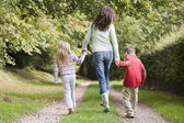 Mother and children walking on woodland path — Stock Photo