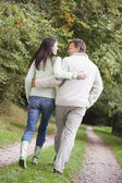 Couple walking along woodland path — Stock Photo