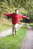 Young boy running along woodland path — Foto Stock