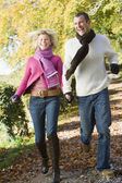Young couple running along woodland path — Stock Photo