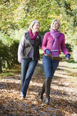 Mother and grown up daughter on walk through woods — Stockfoto