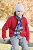Młody chłopak siedząc na płocie — Zdjęcie stockowe