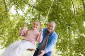 Grandfather pushing granddaughter on swing — Stock Photo