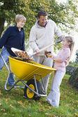 Kinderen helpen vader te verzamelen herfstbladeren — Stockfoto