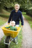 Boy pushing toddler in wheelbarrow — Stock Photo