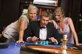 Man with glamorous women in casino — Zdjęcie stockowe