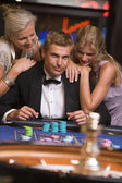 Man gambling in casino surrounded by attractive women — Stock Photo