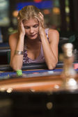 Woman losing at roulette table — Stockfoto
