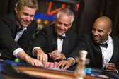 Group of male friends at roulette table — Stock Photo