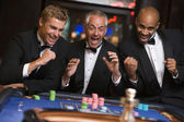 Group of men celebrating win at roulette table — Stock Photo