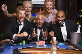 Group of friends celebrating at roulette table — Stock Photo