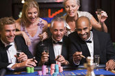 Group of friends gambling at roulette table — Stock Photo