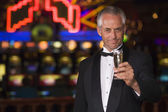 Man in tuxedo drinking champagne in casino — Stock Photo