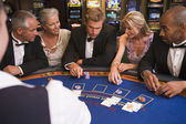 Group of friends playing blackjack in casino — Stock Photo